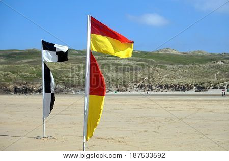 Flags On A Deserted Beach Indicating Safe Swimming And Surfing Zones