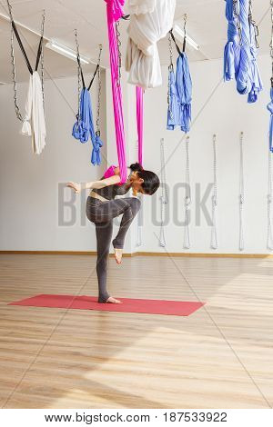 Anti gravity aerial yoga concept. Woman exercises with shoulders bounded by hammock standing on one leg in hip-opening yoga pose with hands stretched to sides