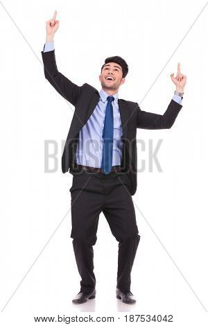 full body picture of an excited businessman pointing fingers and looking up on white background
