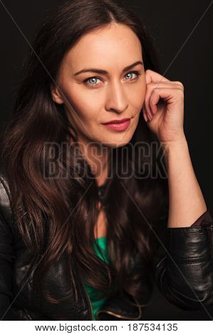 portrait smiling woman looking pensive on dark background