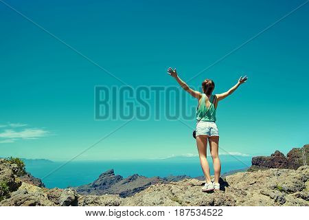 Happy Stylish Girl Woman In Casual Hipster Clothes Standing On The Cliff Of Mountain With Raised Han