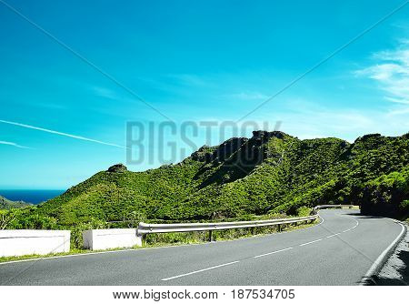 Turning Mountain Highway With Blue Sky And Empty Rural Asphalt Perspective With White Line Road