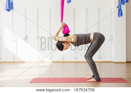 Woman stretches back holding hands on hammock and going to jump on it. Aerial antigravity yoga pose, woman does exercises, meditate in calm position trying to achieve harmony