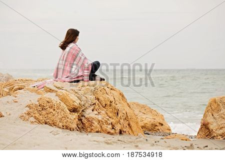 Young woman is covered with a rug sits on the seashore and drinking hot tea (coffee) from a thermos bottle. Selective focus.