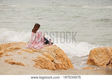 Young woman is covered with a rug sits on the seashore and reads an ebook. Selective focus.