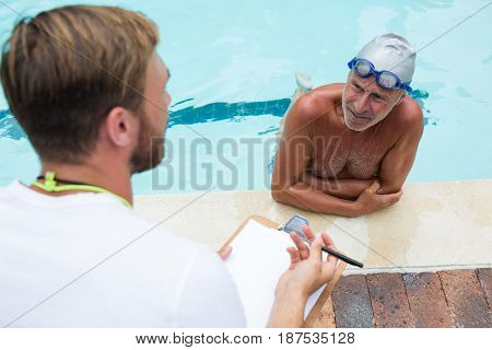Swim coach interacting with senior man at poolside