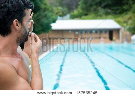 Lifeguard looking at swimming pool and blowing whistle on a sunny day