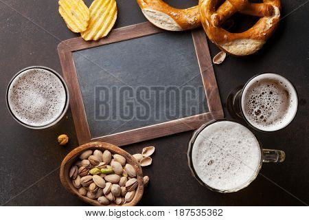 Lager beer and snacks on stone table. Nuts, chips, pretzel. Top view with chalkboard for copy space