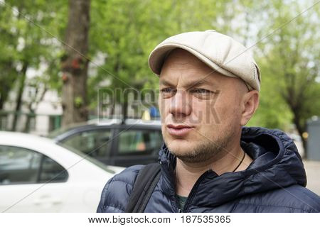 Adult man in a cap and demi-season jacket in a city street
