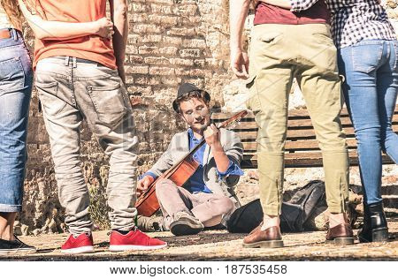 Young people watching street artist performer playing acoustic classic guitar outdoors - Adventure lifestyle concept with musician guy earning money with artistic skills - Warm afternoon filter tones