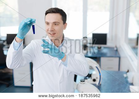 Medical discovery. Attractive smiling analyst keeping test glass in right hand and pointing at it with left hand while looking very glad
