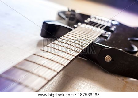 Electric guitar on old wooden surface .