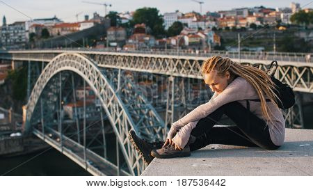 Young woman with blond dreadlocks sitting on the background of Dom Luis I bridge, Porto, Portugal.
