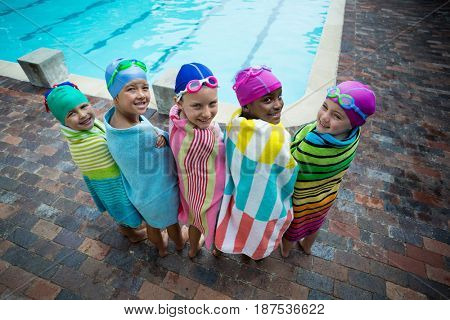 Rear view of little swimmers wrapped in towels standing at poolside