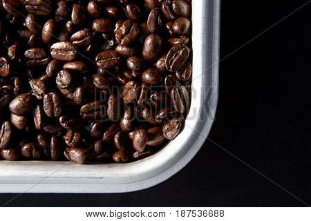 Roasted coffee beans in a metal tray on black background