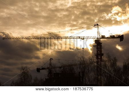 Construction cranes in front of sunset - silhouette, telephoto