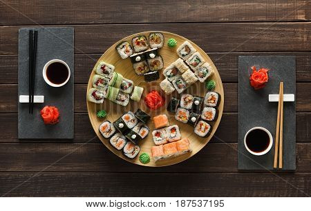 Japanese restaurant, sushi roll platter top view on rustic wood background and black slate plates.. Set for two with chopsticks, ginger, soy, wasabi.