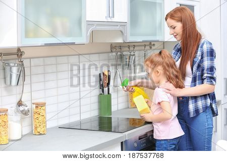 Little girl and her mother cleaning electric stove in kitchen at home