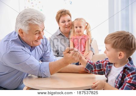 Happy senior man and his grandson having arm wrestling competition at home
