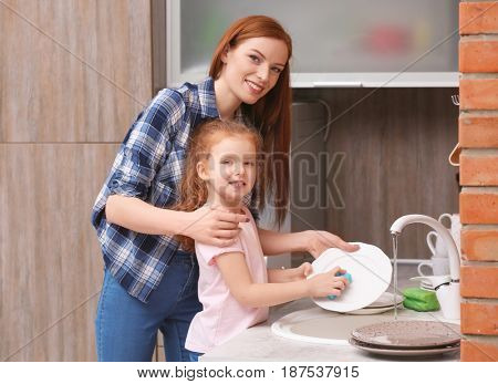 Little girl and her mother doing the washing-up in kitchen at home