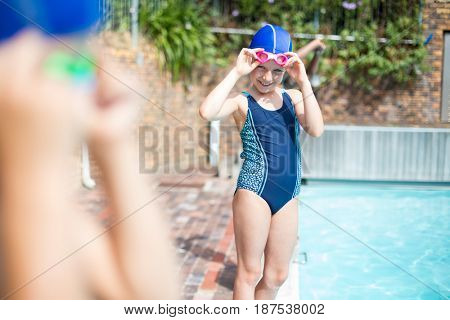 Portrait of little girl wearing swimming goggle at poolside