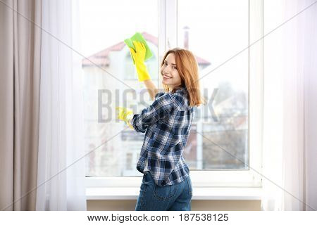 Young woman using rag while cleaning window in light room