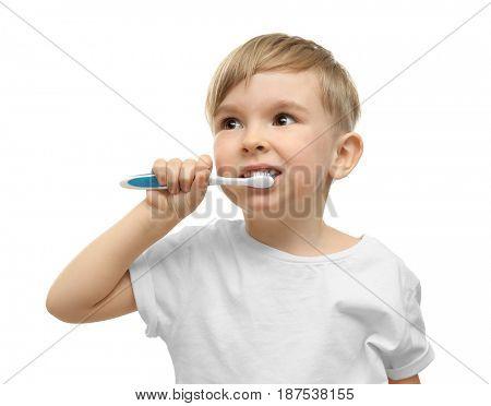 Cute little boy brushing teeth on white background