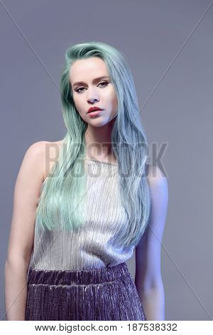 Trendy hairstyle ideas. Young woman with mint hair color on gray background