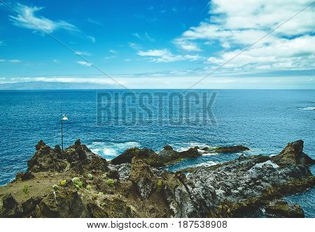 Beautiful View From The Cliff Of Mountain To The Ocean With Blue Sky And Clouds