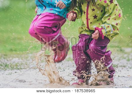 Children In Rubber Boots And Rain Clothes Jumping In Puddle.