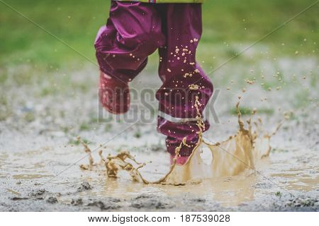 Children In Rubber Boots And Rain Clothes Jumping Puddle Defocused.
