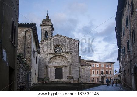 SAN QUIRICO D'ORCIA,ITALY-APRIL 24,2016::people stroll near the church in the San Quirico town square during a cloudy day.