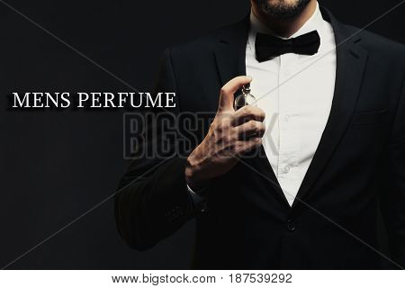 Men's perfume. Man using cologne and text on dark background