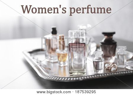 Women's perfume. Tray with bottles of scent on table
