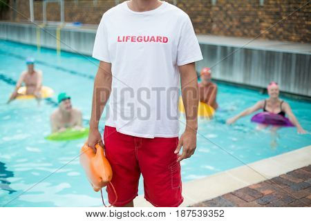 Mid section of male lifeguard holding rescue can while standing at poolside