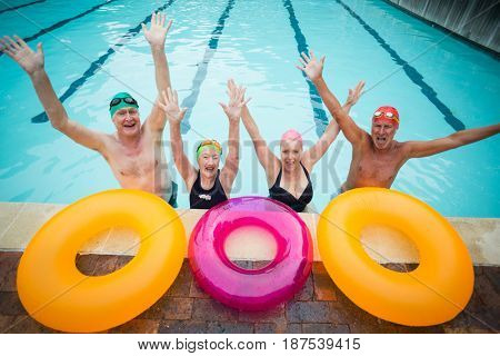 High angle view of cheerful senior swimmers with inflatable rings at poolside