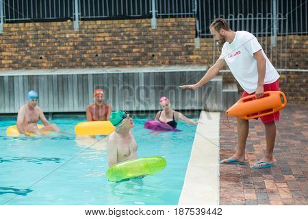 Male lifeguard helping swimmers at poolside