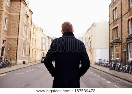Rear View Of Man Walking Along Residential Street In Oxford