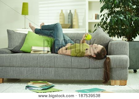 Young woman lying on sofa at home, holding apple, listening to music, books scattered around.