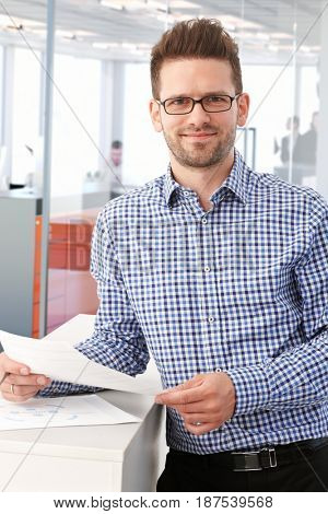 Casual young businessman reading papers, smiling, looking at camera.