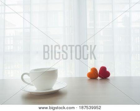 wood office table with white coffee cup and couple sweet heart sign on blurry beautiful white drape window texture background. concept of coffee break.