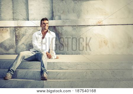 Model handsome man relaxed and sitting on the steps of white marble. Casual clothes, wearing white shirt and jeans. Outdoor, near a historic white marble building. Light spot to the right.