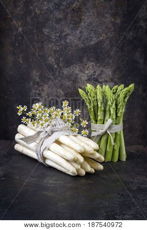 Row white and green Asparagus with flower as close-up on an old rustic metal sheet