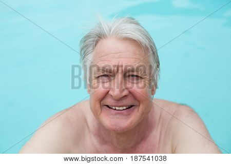 Portrait of happy senior man swimming in pool