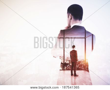 Back view of young businessman looking into the distance on light city background with copy space. Research concept. Double exposure