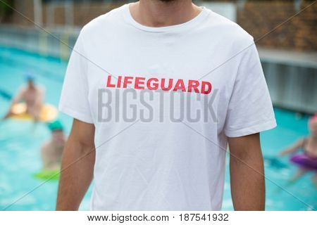 Mid section of male lifeguard standing at poolside