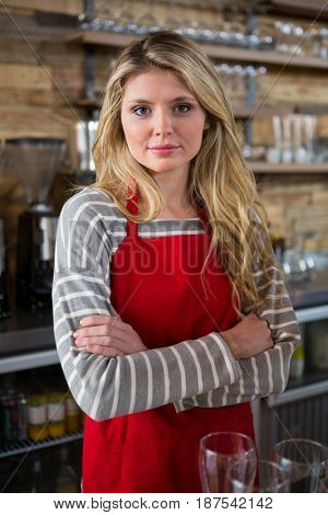Portrait of young female barista standing arms crossed in coffee shop