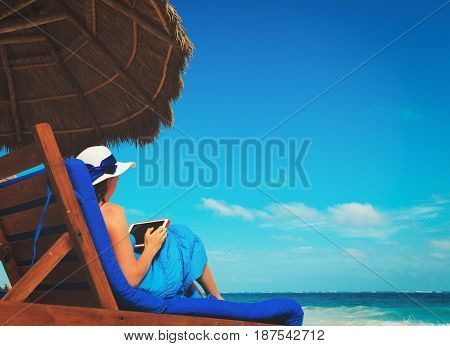 woman with touch pad on tropical beach