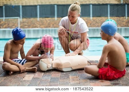 Female lifeguard helping children during rescue training at poolside