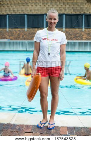 Portrait of confident female lifeguard holding rescue can at poolside